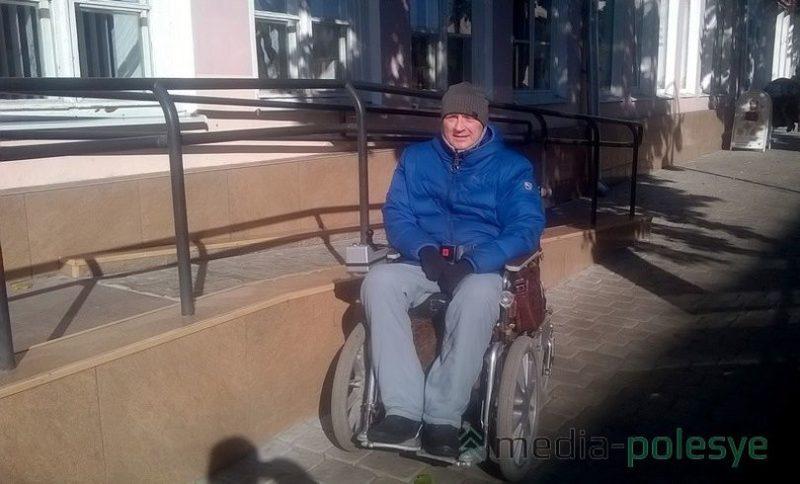 Валерий Тимакин у пандуса, которым невозможно воспользоваться колясочнику, так как дверь аптеки открывается в сторону пандуса