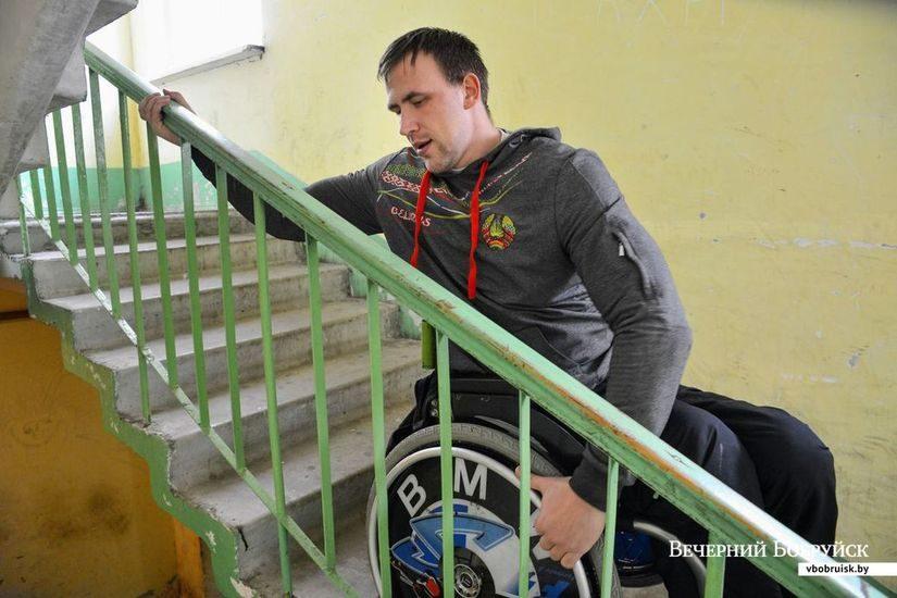 Спортсмен-гребец инвалид-колясочник Андрей Ткачук поднимается по лестнице в подъезде своего дома.