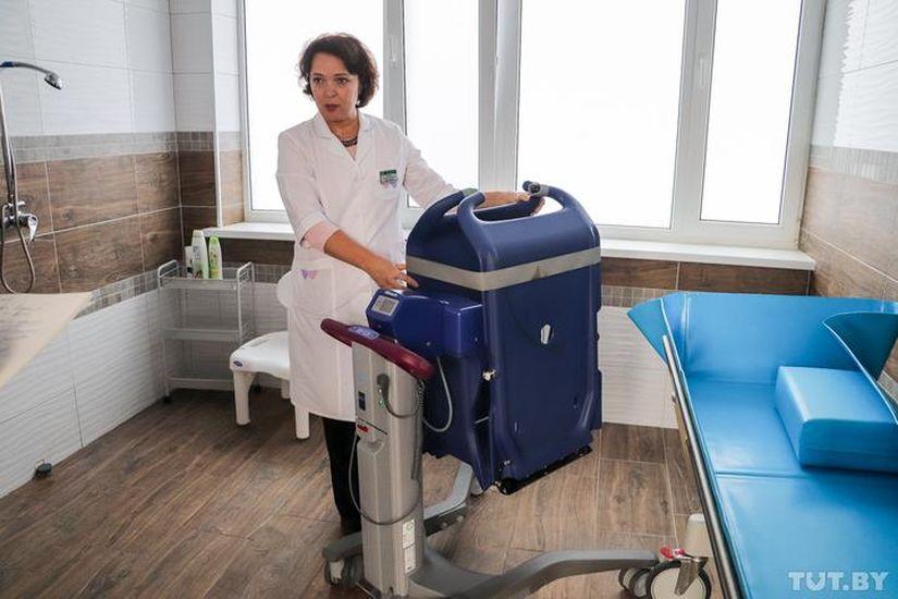 Людмила Жилевич показывает раскладную тележку: нанее лежачего пациента перекладывают скровати, апотом везут вванную мыться